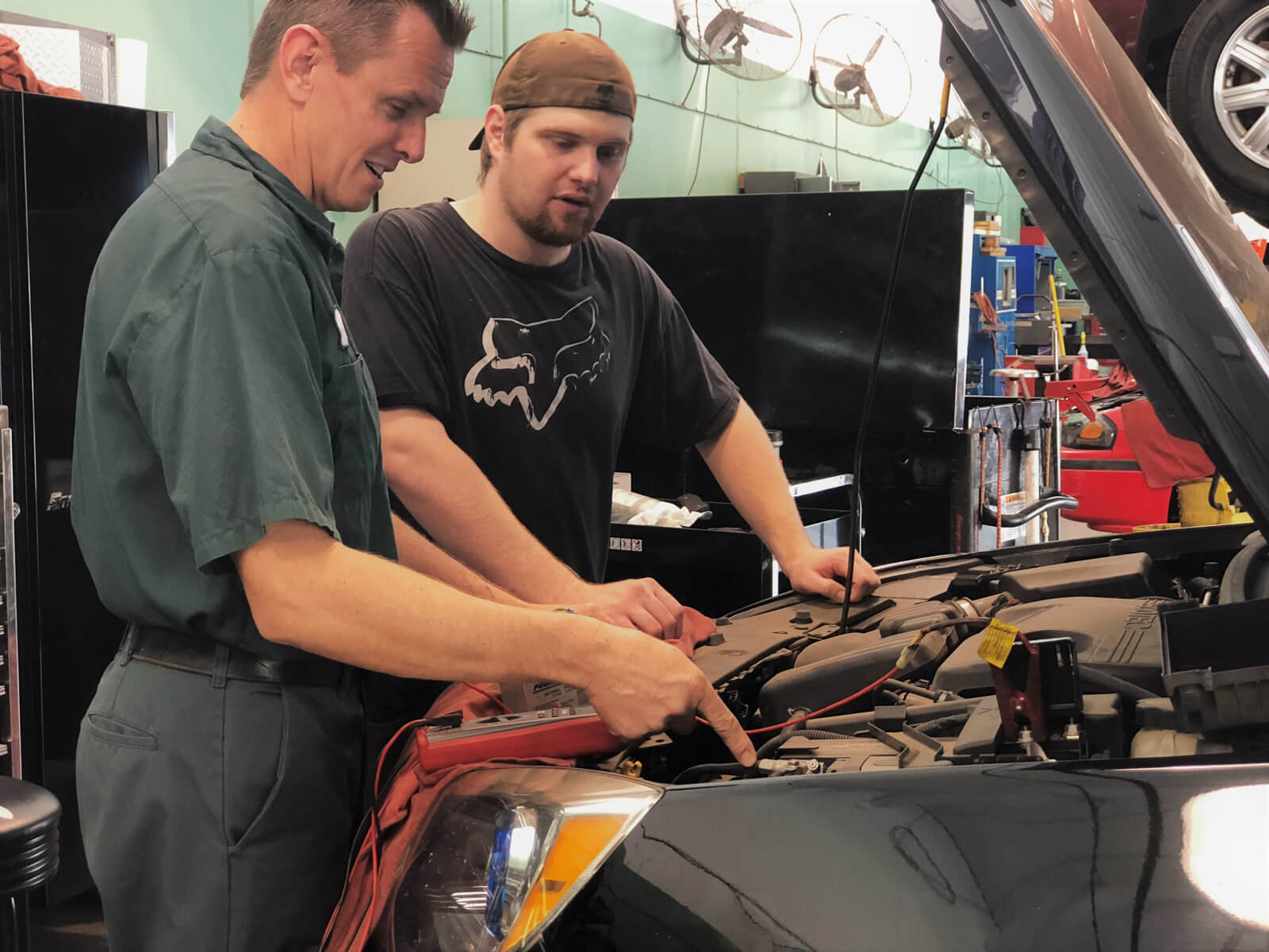 Two mechanics looking into the front of a car for maintenance